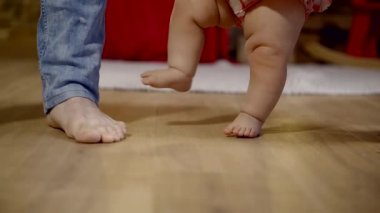 parents are teaching baby girl to walk, close-up shots of their feet, camera is moving to childs face