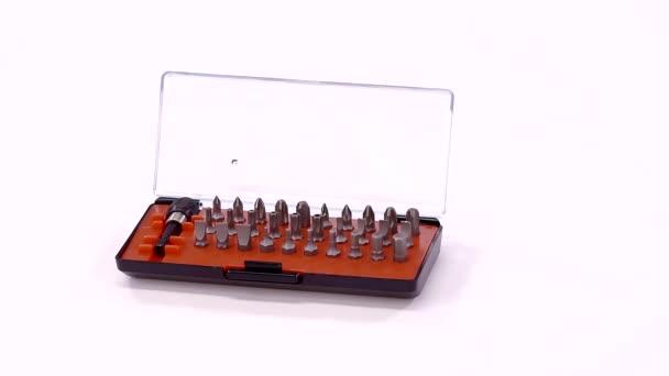 šroubovák s bity v malé otevřené pole stojí na bílá rotační stůl, detail