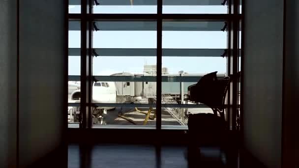 pohled na most jet a letadla z letištní budovy velkými okny, siluetu štíhlé ženy chodí