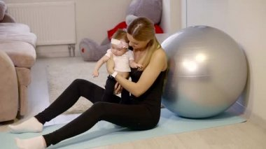 an adult woman resting after a workout, she is holding her daughter in her arms
