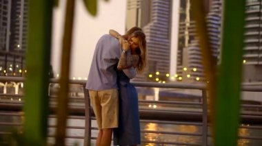 young couple tenderly embrace, the couple stands near the river in the evening,