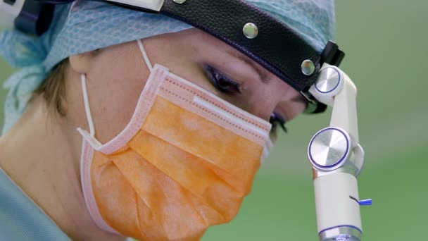 portrét koncentrovaného žena chirurg během provozu, dívá se, světlomet je upevnění na čelo