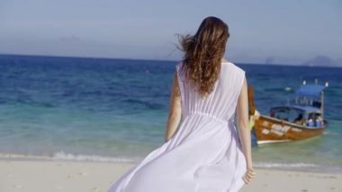 young slim woman with long brown hair is going to a vivid blue sea, her white long dress is waving on a wind
