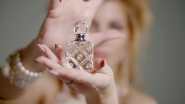 crystal vial with aroma is standing in a hand of blonde, face of woman is out of focus