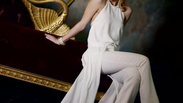 Mode junge Dame trägt weiße Hose und Bluse sitzt und posiert in einem dunklen Studio