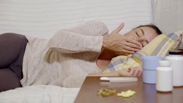 Frau wacht auf einem Sofa auf, berührt ihre Stirn und beschließt, Temperatur zu nehmen