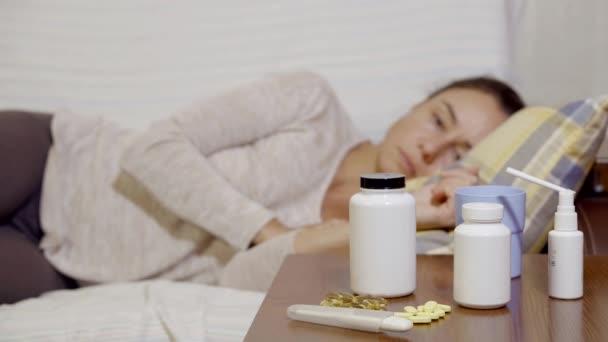 brünette Frau liegt auf einer Couch, fühlt sich schlecht, schaut auf einen Tisch mit Tabletten, nimmt Thermometer