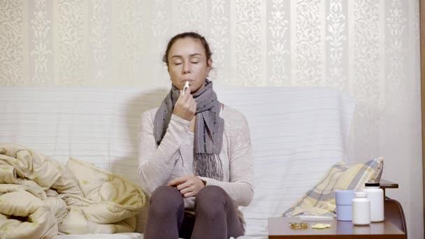 Frau sitzt auf einer Couch und misst die Temperatur mit Thermometer, schaut auf einen Messwert