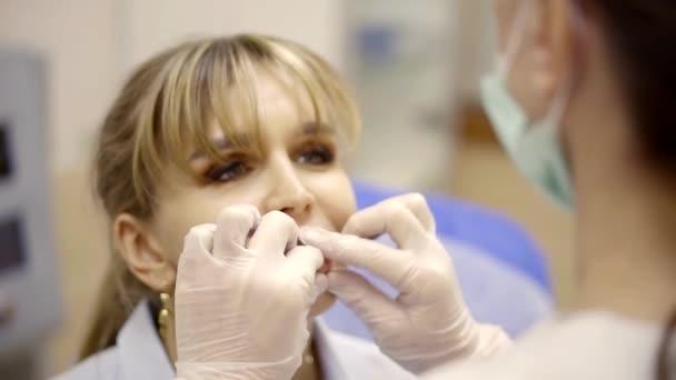 weibliche plastischer Chirurg fühlt sich Patienten Lippen in einer Arztpraxis, Frau blickt auf einen Arzt