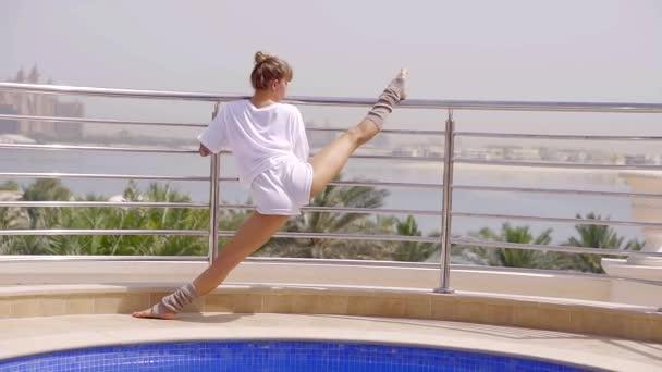 dospělé ženy se táhne povrchu nohy na balkoně, pak raduje a tančí