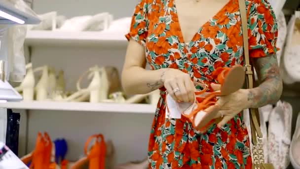 a young woman is shopping, a lady chooses a pair of shoes at the mall
