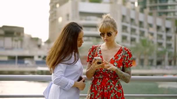 mladí přátelé vybrat hudbu na smartphone, pak ženy tančit na hudbu