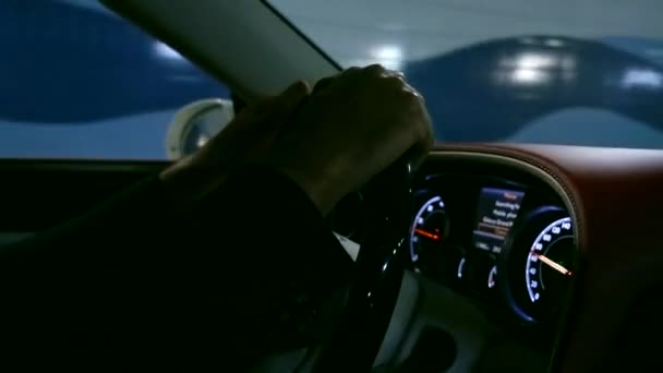 Close up shot of a mans hands on steering wheel in moving car.