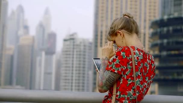 Blondes Mädchen fotografiert moderne Gebäude in der Innenstadt moderner Städte mit ihrem Smartphone, Rückansicht