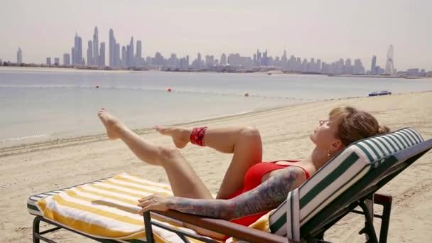 sportovní žena leží na lehátku a dívá na moři a vykonává rotoped pro nohy