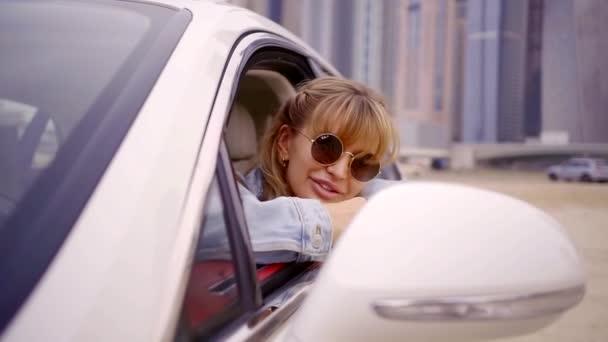 boldog és fiatal nő hozta a fejét az ajtón, a jármű, úgy néz ki, hogy az oldalon, és élvezi a kilátás