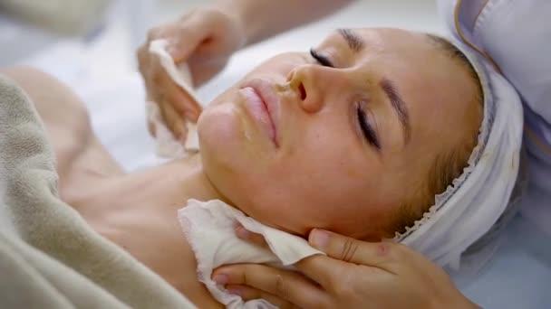 portrét ženy, která spočívá v lázních, kosmetička čistí pleť výživná maska