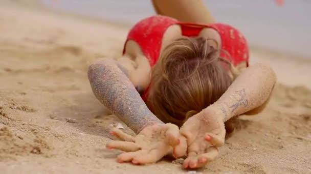 Portrét dámy s velkými hrudníku, který ležel na písku a blbnout