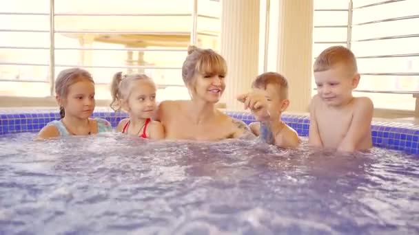 eine große Mutter ist in den Ferien im Pool, neben ihr schwebt ihre ganze große Familie,