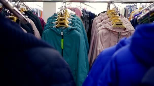 blízko střílel na řad s oblečení, mnoho různých bundy jsou na ramínka v úložišti
