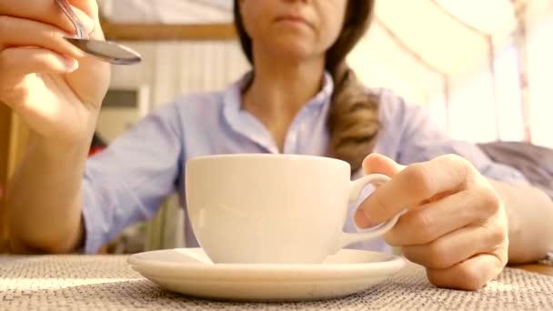Zavřete záběr na mladých ženách rukou, který podněcuje cukru v šálku s lžičkou
