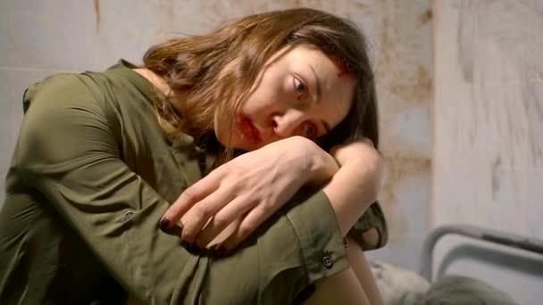Zár megjelöl szemcsésedik-ból egy megverték és kétségbeesett nő ül a kórházi ágyon, átölelve a térdére, és rázza.