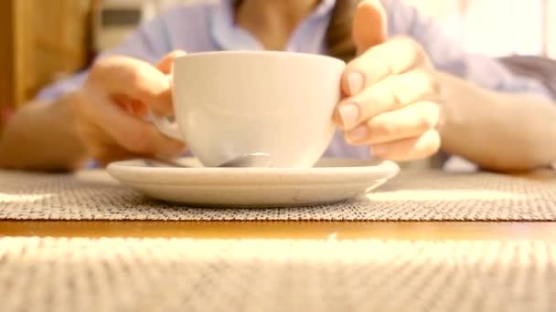 Detail bílý šálek horké ranní kávy na stole, žena bere, popíjení a uvedení zpět