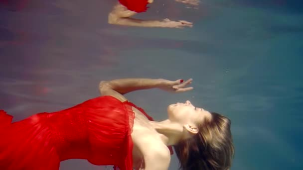 floating girl is moving to surface of water from bottom and touching it, reflecting like in a mirror
