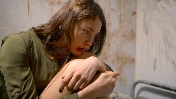 egyedül a boldogtalan nő ül egy kórterem egy Elmegyógyintézet, átölelve térdre, vér az arcán, és a falak