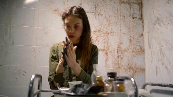 mladá žena se dívá na rukavice, která ležela na stole lékařský, duševně nemocných je uvězněn ve špinavé místnosti