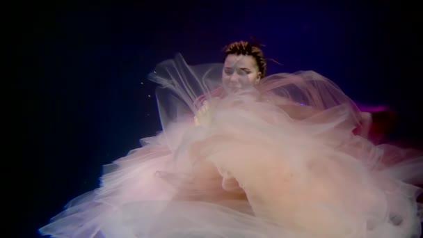 mladá žena jako mořská panna plave pod vodou, ona má dredy na hlavě