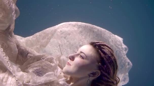 Mladá mořská víla plave pod vodou a těší se na moři chladu během večerní koupání