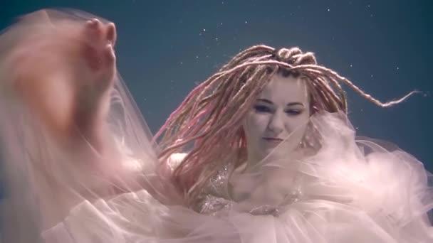 Kouzelné mladá žena s dlouhou růžový dready je představuje sám pod vodou nosit šaty.