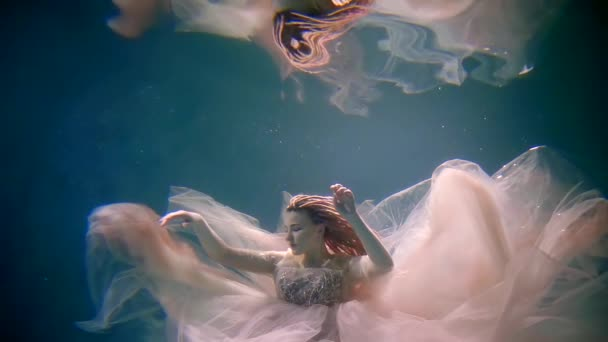 beautiful romantic bride is swimming underwater in pool and her reflection in surface is above her