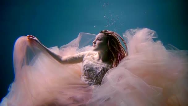 úžasné nevěsta pluje pod vodou v hlubinách moře v modrém pozadí, světle růžové šaty a dredy jsou mává