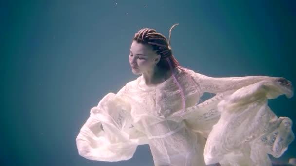elegante, schlanke Frau in einem Spitzenkleid schwimmt im klaren Wasser des Meeres