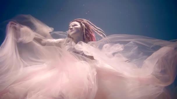 romantikus álom lány úszó víz alatt a tenger, és megható kezek gyönyörű pink ruhája