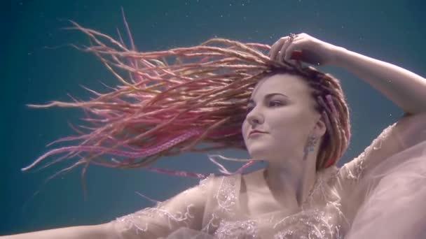 mořská panna s růžový dredy je plovoucí pod vodou, rozhlížel se kolem a pohybující se ruce