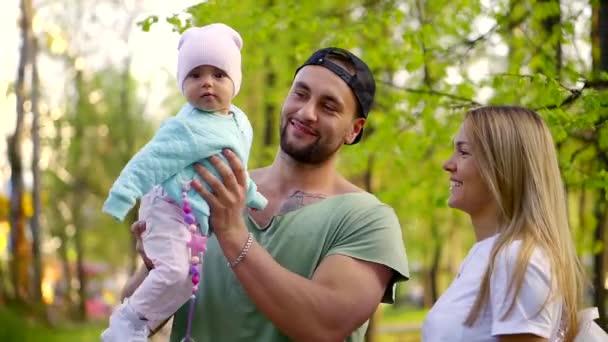 boldog fiatal család nyári parkban urai a csecsemő, férfi gazdaság gyerek kezét, anya sétálnak, közelében