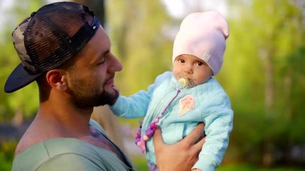 vidám apja csecsemő tartja a kezét, és séta a parkban a tavaszi nap, az ember mosolyog