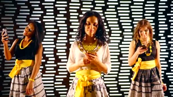 three multi ethnic girls are standing in night club on dance floor and looking on screens of phones