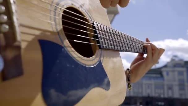 Close-up  acoustic guitar and hand of the musician plectrum hitting the  strings produces the sound  the practice of playing a musical instrument on  the street