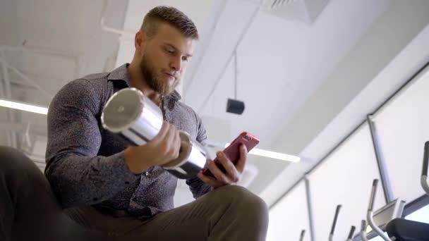 Obchodní mužského kulturista biceps vlaky zvednutím činka s jednou rukou v business stylu oblečení drží mobilní telefon na druhé straně vytočí textovou zprávu