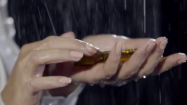close-up shot of beautiful womans hands, holding small yellow vial with delightful essential oil