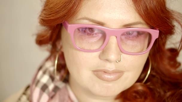 elegantní mladá zrzka žena nosí stylové moderní živé růžové brýle a piercing do nosu