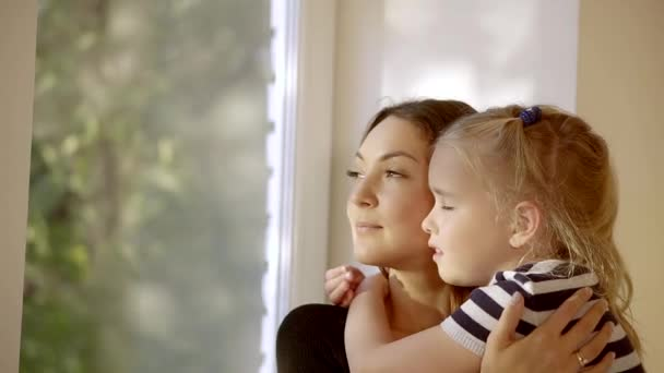 charming mother and daughter are embracing, standing near big window and looking on outside