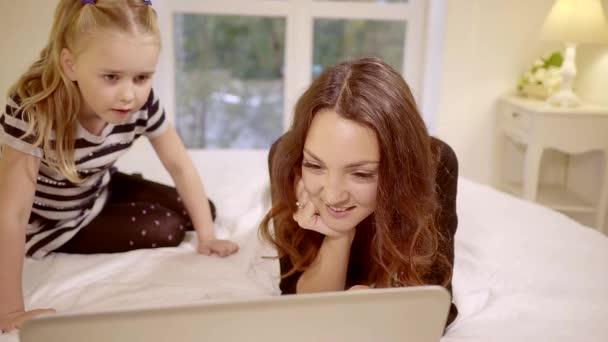 anya és aranyos kis lánya néz vicces video-ra egy laptop számítógép, egy ágyon