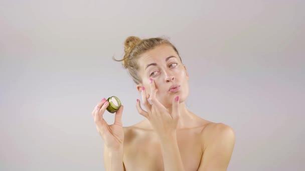 legrační štíhlá blondýnka s nahá ramena je použití oční krém, denní kosmetické ošetření