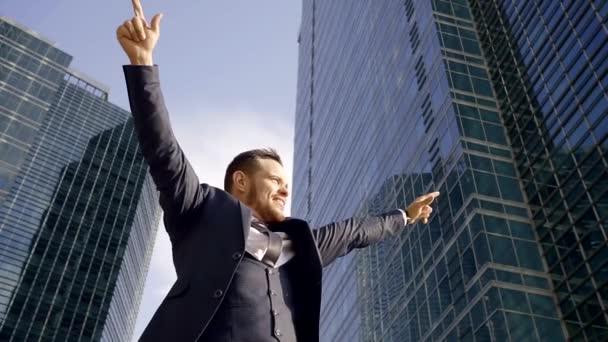 selbstbewusster und fröhlicher junger Mann mit erhobenen Händen lächelt, steht im Hintergrund der Gebäude