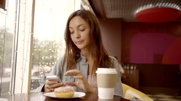 hnědovlasá dívka má na sobě ležérní styl sedí v kavárně s kávou a kobliha